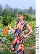 Женщина держит в руке пучок крупной моркови, фото № 6808371, снято 16 декабря 2014 г. (c) FotograFF / Фотобанк Лори