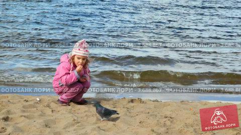 Кормит голубей на берегу реки осенью