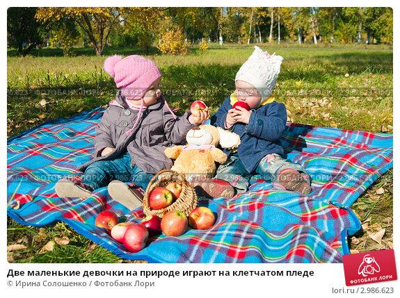 Две маленькие девочки на природе играют на клетчатом пледе; фотограф