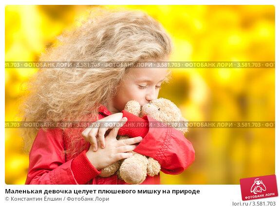 Маленькая девочка целует плюшевого мишку на природе; фотограф