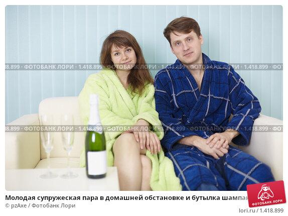 Молодая супружеская пара в домашней обстановке и бутылка шампанского