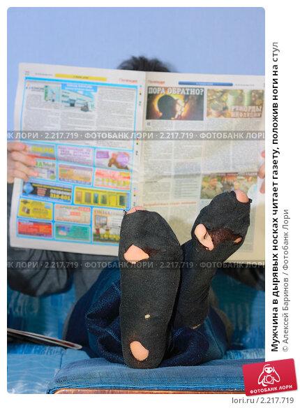 Мужчина в дырявых носках читает газету, положив ноги на стул, фото 2217719, снято 2 декабря 2010 г. (c)...