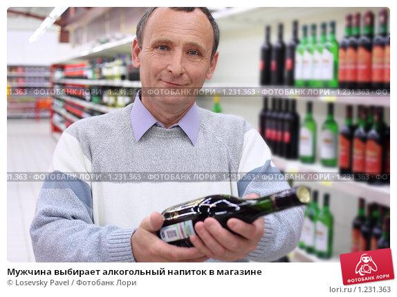 Мужчина выбирает алкогольный напиток в магазине, фото 1231363.