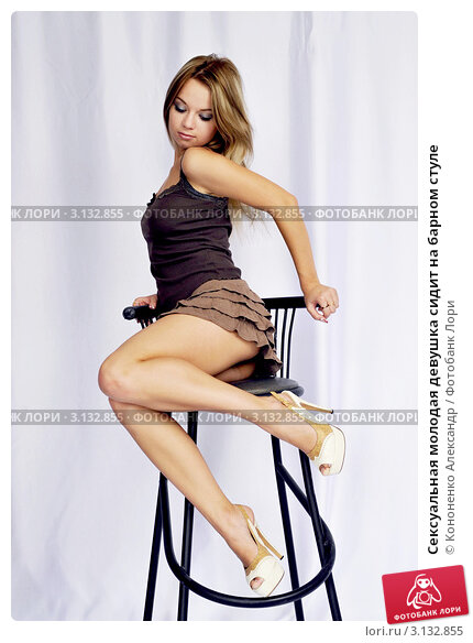 Сексуальная молодая девушка сидит на барном стуле; фотограф Кононенко