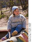 Купить «Ребенок сидит на раскрашенной покрышке на детской площадке ранней весной», фото № 127107, снято 29 апреля 2007 г. (c) Ольга Сапегина / Фотобанк Лори