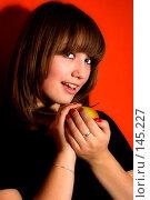Купить «Игривая девушка с желтым яблоком», фото № 145227, снято 18 ноября 2007 г. (c) Петухов Геннадий / Фотобанк Лори