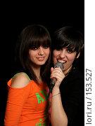 Купить «Две девушки с микрофоном в руках на черном фоне», фото № 153527, снято 4 мая 2007 г. (c) Александр Паррус / Фотобанк Лори