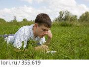 Молодой человек читает книгу, лежащую на траве. Стоковое фото, фотограф Катыкин Сергей / Фотобанк Лори