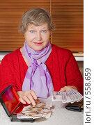 Купить «Женщина пенсионного возраста перекладывает деньги в шкатулку из кошелька», фото № 558659, снято 13 ноября 2008 г. (c) Ольга Кедрова / Фотобанк Лори