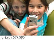 Две девочки смотрят на экран сотового телефона. Стоковое фото, фотограф Сайганов Александр / Фотобанк Лори