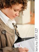 Купить «Молодая девушка, подписывающая документы», фото № 597127, снято 15 ноября 2008 г. (c) Дмитрий Яковлев / Фотобанк Лори