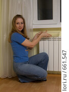 Купить «Молодая женщина ставит на отопительную батарею емкость с водой», фото № 661547, снято 18 января 2009 г. (c) Тимур Ахмадулин / Фотобанк Лори
