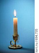 Купить «Горящая свеча в бронзовом подсвечнике на голубом фоне», фото № 694735, снято 3 февраля 2009 г. (c) Андрей Ганночка / Фотобанк Лори
