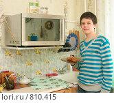 Купить «Юноша собирается разогреть еду в микроволновке», фото № 810415, снято 28 марта 2009 г. (c) Ирина Солошенко / Фотобанк Лори