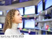 Купить «Молодая женщина смотрит на телевизоры в магазине», фото № 810959, снято 21 октября 2018 г. (c) Losevsky Pavel / Фотобанк Лори