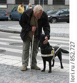 Слепой мужчина благодарит собаку-поводыря на улице Праги. Редакционное фото, фотограф Ирина Борсученко / Фотобанк Лори