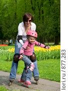 Купить «Мама с дочкой катаются на роликах в парке. Фокус на девочке», фото № 877283, снято 10 апреля 2009 г. (c) Алексей Кузнецов / Фотобанк Лори