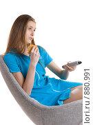 Купить «Девушка с пультом от телевизора сидит на кресле и жует бутерброд», фото № 880991, снято 26 марта 2009 г. (c) Кувшинников Павел / Фотобанк Лори