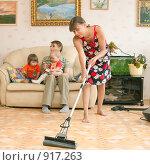 Купить «Уставшая женщина убирается, а семья отдыхает на диване», фото № 917263, снято 13 июня 2009 г. (c) Ирина Солошенко / Фотобанк Лори