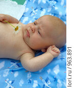 Хмурящийся младенец с ромашкой в руке. Стоковое фото, фотограф Матвеева Наталья / Фотобанк Лори