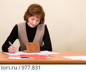 Купить «Девушка заполняет документы, сидя за столом», фото № 977831, снято 22 декабря 2007 г. (c) Барковский Семён / Фотобанк Лори