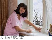Купить «Девушка заклеивает окна», фото № 992427, снято 22 июля 2009 г. (c) Кристина Викулова / Фотобанк Лори