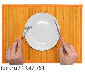 Купить «Столовая сервировка- нож,вилка в руках на желтой  бамбуковой циновке», фото № 1047751, снято 12 июня 2009 г. (c) Vitas / Фотобанк Лори