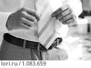 Мужчина в брюках с темным ремнем и белой рубашке держится обеими руками за галстук. Стоковое фото, фотограф Полина Бублик / Фотобанк Лори
