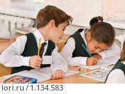 Купить «Школьник на уроке заглядывает соседке в тетрадь», фото № 1134583, снято 22 сентября 2009 г. (c) Федор Королевский / Фотобанк Лори