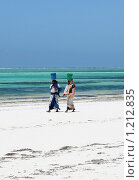 Занзибарские аборигенки в красном на берегу океана несут груз на головах (2008 год). Редакционное фото, фотограф Димитрий Сухов / Фотобанк Лори