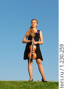 Купить «Girl with violin stands on grass against  sky», фото № 1230259, снято 23 июня 2009 г. (c) Losevsky Pavel / Фотобанк Лори