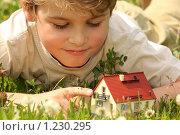 Купить «Мальчик лежит на траве и держит в руках макет дома», фото № 1230295, снято 28 июня 2009 г. (c) Losevsky Pavel / Фотобанк Лори