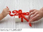 Купить «Рука ребенка и рука женщины открывают подарок», фото № 1245607, снято 25 ноября 2009 г. (c) Дарья Петренко / Фотобанк Лори