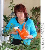 Купить «Красивая женщина ухаживает за комнатными цветами на лоджии», эксклюзивное фото № 1407143, снято 23 января 2010 г. (c) Юрий Морозов / Фотобанк Лори