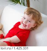 Купить «Девочка сидит на диване и смеется», эксклюзивное фото № 1425331, снято 12 ноября 2009 г. (c) Juliya Shumskaya / Blue Bear Studio / Фотобанк Лори