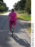 Девушка на велосипеде едет по сельской дороге (2009 год). Редакционное фото, фотограф Федор Болба / Фотобанк Лори