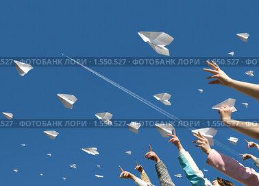 Детские руки запускают в небо бумажные самолетики