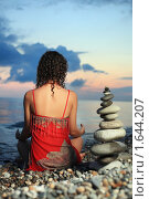Купить «Красивая женщина в красном сарафане сидит рядом с пирамидой из гальки», фото № 1644207, снято 9 июля 2009 г. (c) Losevsky Pavel / Фотобанк Лори