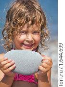 Купить «Улыбающаяся хорошенькая девочка держит в руках камешек», фото № 1644699, снято 19 июля 2009 г. (c) Losevsky Pavel / Фотобанк Лори