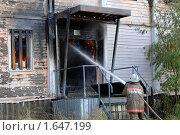 Пожарный тушит крыльцо горящего дома. Стоковое фото, фотограф Евгений Волдаев / Фотобанк Лори