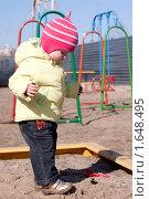 Ребенок в песочнице на фоне детской площадки весной. Стоковое фото, фотограф Марина М. / Фотобанк Лори