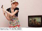 Женщина разбивает телевизор. Протест против засилия телевидения в семье. Стоковое фото, фотограф Валерий Степанов / Фотобанк Лори
