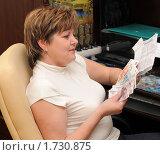 Купить «Женщина средних лет с деньгами и коммунальными платежами», эксклюзивное фото № 1730875, снято 26 мая 2010 г. (c) Юрий Морозов / Фотобанк Лори