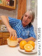 Купить «Мужчина занят приготовлением апельсинового фреша в домашних условиях», фото № 1795695, снято 25 июня 2010 г. (c) Анна Мартынова / Фотобанк Лори