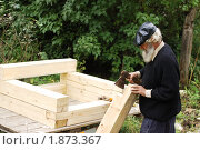 Пожилой плотник делает сруб из бруса (2008 год). Редакционное фото, фотограф Артем Костров / Фотобанк Лори