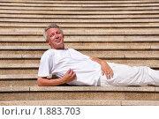 Купить «Веселый седой мужчина лежит на ступеньках», фото № 1883703, снято 1 августа 2010 г. (c) Константин Бредников / Фотобанк Лори