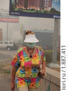 Прохожая в кепке и защитной повязке на лице. Из-за гари нечем дышать и режет глаза (2010 год). Редакционное фото, фотограф Константин Сутягин / Фотобанк Лори