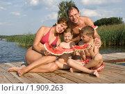 Счастливая семья с двумя детьми в солнечный день на фоне реки с дольками арбуза в руках. Стоковое фото, фотограф Julia Ovchinnikova / Фотобанк Лори