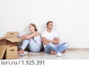 Молодая поссорившаяся пара распаковывает коробки после переезда. Стоковое фото, фотограф Raev Denis / Фотобанк Лори