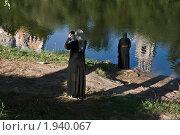 Торжок. Монахини-туристки фотографируют на берегу р. Тверца, в которой отражается Борисоглебский монастырь. Стоковое фото, фотограф Ирина Фирсова / Фотобанк Лори